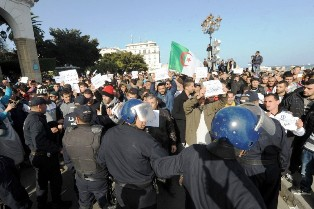 "Algerian riot police monitors as people take part in a demonstration against French satirical weekly Charlie Hebdo for publishing a cartoon of the Muslim prophet Mohammed on January 16, 2015 in the capital Algiers. Between 2.000 and 3.000 take part in the protest as Muslims marched as well in Middle Eastern cities against the latest cartoon published by Charlie Hebdo featuring the Prophet Mohammed on its cover holding a ""Je Suis Charlie"" sign under the headline ""All is forgiven"".  AFP PHOTO / STR"